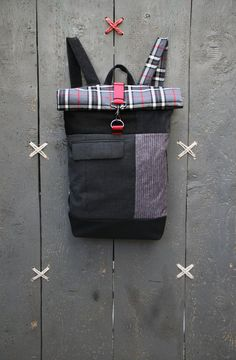 "Checkered black,grey and red roll top rucksack with an opening on the back for quick access to your things, by ""Eating The Goober"""