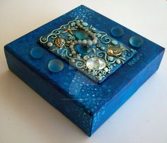 Found a wooden box at a garage sale and covered it in polymer clay, glass gems, glass cats eye cabochons and shimmery dyed shell beads. Accented with metallic paint. Burgandy velvet interior. It me...