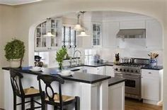 Peninsula with raised bar top, white cabinets, dark counters, chrome bridge faucet