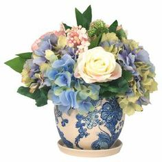"""Showcasing hydrangea, rose, and lilac blooms, this lovely faux floral arrangement lends a touch of natural appeal to your living room or kitchen.   Product: Faux floral arrangementConstruction Material: Silk, polyester and ceramicColor: Blue, red and purpleFeatures:  Includes hydrangeas, baby roses and lilacsCeramic baseDimensions: 14"""" H x 14"""" Diameter"""