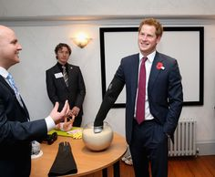 Prince Harry wears a glove to experience what it is like to have a brain injury as he opens the new headquarters of Headway, the brain injury charity
