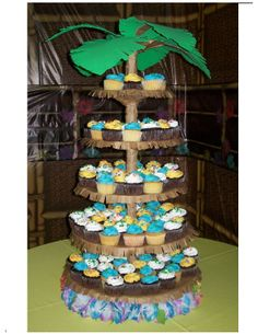 """Palm Tree Cupcake Tower for Promotion Dance - This was for an 8th grade promotion dance with an """"Island Paradise"""" theme.  We needed 300 cupcakes, so I decorated 4 cupcake cakes (in my photo gallery) and put the rest on the cupcake tower.  The tower is actually the tall tier wedding cake stand converted with brown paper, green fun foam, and hot glue."""