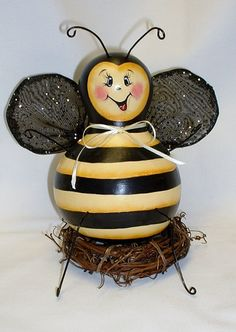 My Bee gourd is 6 tall and 13 around. His arms, legs and antenna are made of wire and painted black. His wings are wire and covered with black glitter netting. He sets on a grapevine wreath. Sealed with satin varnish, signed and dated by me. Thank you for looking at my work.