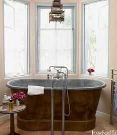 Antiques and patina dominate the decor in designer Penelope Bianchi's Santa Barbara home. One of her favorite features is this 1860s zinc-lined copper tub, surrounded by a trio of windows. Click through for more designer bathrooms to inspire your next reno.