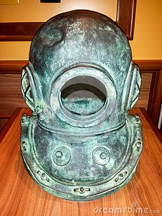 Old diver helmet used for deep water diving with breathing gas (air) supplied from the surface.  The helmet is corroded and has a dent. The diving helmet is sitting on a wooden table.