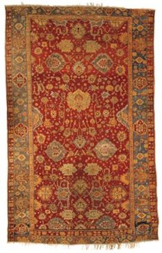 USHAK CARPET  WEST ANATOLIA, CIRCA 1880  Of Agra design, the blood-red field with a counterposed design of large palmettes and occasional cloudband linked by angular flowering tendrils, in a shaded light blue palmette and flowering vine border between tan floral meander and red flowerhead and floral spray stripes, corroded black, a few areas of localised wear, one end border missing and replaced by half the other, possibly reduced in length 17ft.11in. x 11ft.4in. (546cm. x 344cm.)
