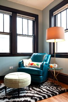 small seating area, bright blue chair, light blue walls, animal striped rug that coordinates with dark wood trim, floor lamp for extra reading light, comfortable upholstered ottoman