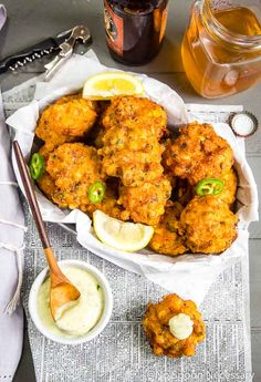 Overhead shot of a basket filled with Lobster and Bacon Corn Fritters, with a small bowl of jalapeno-honey aioli and spoon in the corner; with lemon wedges, jalapeno slice., beer, beer cap and newspaper in the background