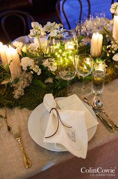 A romantic table is lined with moss enveloped in white florals, pillar candles and bell jars.