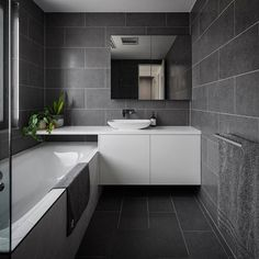 The Dept. of Design Canberra - a residential bathroom interior featuring one of our charcoal tiles with grey undertones. Using the same tile floor and wall creates a seamless look as there is no point of break. This bathroom looks indulgent!