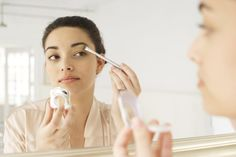 Mujer frente a un espejo pintándose un ojo