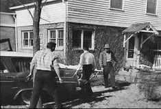 En la parte posterior de la casa de la familia Clutter, el Sheriff Earl Robinson (con sombrero) dirige el traslado  de los cuerpos de Herbert, Bonnie, Nancy y Kenyon. Era la mañana del domingo 15 de noviembre de 1959.  La puerta que se observa es una de las cuatro entradas a la casa y daba acceso a la cocina. Por esta puerta ingresaron Nancy Ewalt y Susan Kidwell buscando a Nancy Clutter. También lo hicieron el Sheriff Robinson, el Sr. Ewalt y Larry Hendricks para investigar lo que sucedía.