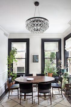 black trim around windows, oval table, mod crystal chandelier