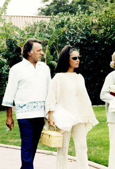 Elizabeth Taylor, in a very mod crocheted look with a wicker bag and head scarf, on holiday with Richard Burton, February 1982.