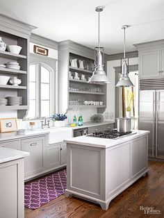 Not to be relegated to simply workroom status, the kitchen carries the home's glamorous aura with aplomb. Gray cabinetry and sleek white countertops convey effortless sophistication, while wide-plank wood floors warm up the space.  an amethyst runner provides a just-right infusion of color.