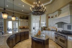 """Large kitchen with custom """"Cosmo"""" level four granite, Viking double oven and six burner range w/custom vent hood, wood front refrigerator and huge island."""