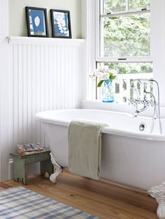 Wainscoted walls—wood paneling that reaches halfway up the wall—embrace the history of this old Vermont home while adding a sense of permanence and durability to the bathroom. via @Country Living Magazine #OmegaVanityMakeover