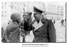 An Italian soldiers stands guard as the German general walks in