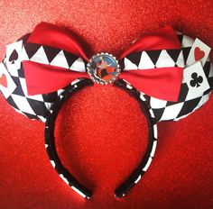 Queen of Hearts, from Alice in Wonderland, Ears made from diamond shaped fabric both on the front of the ears and back, attached mini cards, Queen of Hearts image, and ruby red bow. All ears are hand crafted and lined with fleece for comfortable wear. Hand attached to head band.