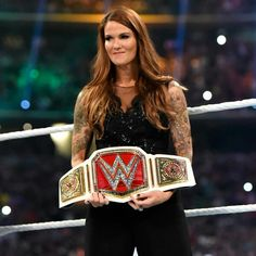 WWE HOF, Lita, holding the WWE Women's Championship before the Women's Triple Threat match at Wrestlemania 32.