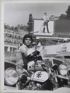 """This is a rare, original publicity photo from the 1982-83 season of """"CHiPs."""". Ponch (Erik Estrada) becomes a celebritywhen a part-time modeling job results in his likeness being emblazoned on a huge Sunset Boulevard billboard as part of a national advertising campaign by a jeans manufacturer. 