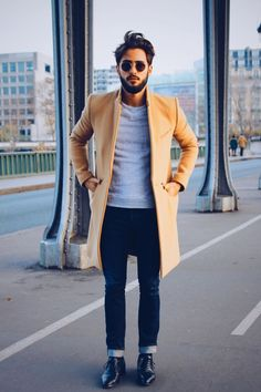 Shop this look on Lookastic: http://lookastic.com/men/looks/sunglasses-crew-neck-sweater-overcoat-skinny-jeans-derby-shoes/7837 — Dark Brown Sunglasses — Grey Crew-neck Sweater — Camel Overcoat — Navy Skinny Jeans — Black Leather Derby Shoes