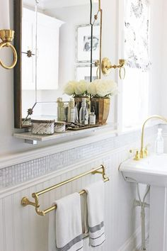 Interior Design Makeover Tips: Vintage Glam on a Budget -- love all of the traditional antique brass fixtures (towel rods, wall sconces, framed vanity mirror, vanity tray, julep cup, and sink faucet) paired with the tiny shimmering line of tiles all the wall around the bathroom, against the all-white millwork.