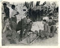 """""""Felled by Jap fire in the invasion of Saipan, a wounded Marine recieves an injection of blood plasma at a beach first aid station as fellow Marines and Coast Guardsmen watch the tense drama of a """"fight for life"""" behind the lines. Blood plasma, again at Saipan, reduced the toll of lives lost in the forces of American Marines, soldiers, sailor, and Coast Guardsmen."""" 1944"""