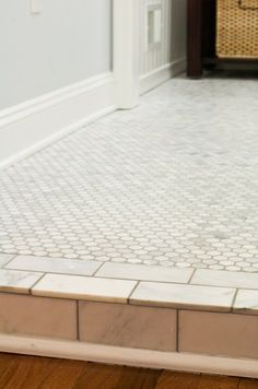 Carrara Marble Hex Tiles with wood trim and a marble threshold