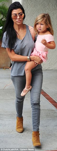 Putting on a brave face: While Kourtney is carrying on as normal for the children, she looked sad as she carried Penelope to class