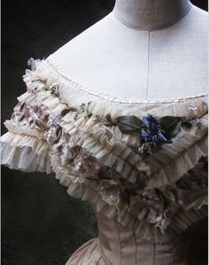 original 1861 evening dress bertha of tulle and flowers.  Note the differences in how the use of the types of net and faux flowers can make it look like it is the real deal or a using the wrong net and flowers, a masquerade costume that screams mainstream.