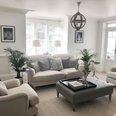 neutral traditional living room design with leather ottoman and chandelier, traditional neutral family room design