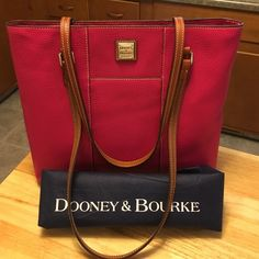 """Dooney & Burke Pebble Lexington Shopper Large Dooney & Burke Lexington shopper with 12"""" drop double handles. It has two pockets on the outside, one on the front and one on the back along with the normal Dooney and Burke pockets on the inside. The color is strawberry and it comes with the dust bag. No stains, marks or damage of any kind. It is new with the tags, see pics. Dooney & Bourke Bags Satchels"""