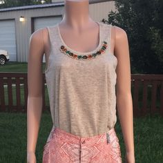 Beige dressy tank top by Chenault • Beige top with dressy neckline to help dress a outfit up when worn with the right accessories, or can be paired with shorts or jeans.                                                                      • Size small                                                               • Made in the U.S.A. By the brand Chenault      •Made of 53% viscose and 47% Polyester.  •Trust me Ladies! You don't want to pass on this one. Chenault Tops Tank Tops