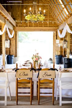 "Rustic sweetheart chair decor idea - ""bride"" + ""groom"" written on wooden chairs tied with navy blue ribbon {Jacquie Rives Photography, LLC}"