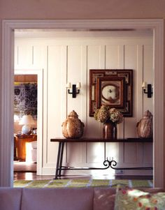 In the front entry hall, a 1950s French wood and iron console table is topped with a pair of antique covered stone ginger jars from Paris.