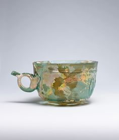 Cup Date: 9th–10th century Geography: Iran or Iraq Culture: Islamic Medium: Glass, blue-green; blown, cut Dimensions: H. 3 1/8 in. (7.9 cm) Diam. 4 13/16 in. (12.3 cm) W. 6 7/16 in. (16.4 cm) Th. at rim 5/32 in. (.4 cm) - See more at: http://metmuseum.com/collection/the-collection-online/search/452063?rpp=90&pg=38&ft=iran&pos=3364#sthash.MzpvCRwd.dpuf