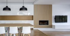 Low-budget idea for a fireplace surround - use strips thin wood evenly spaced along a plain wall.