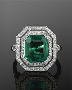Colombian Emerald and Diamond Ring, circa 1915.  An octagonal step cut Colombian emerald weighing approximately 3.50 carats, with accompanying gemological report, is set with a diamond border in a platinum mounting.