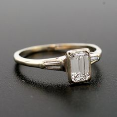 An exquisite estate diamond ring from the 1950's! The center diamond stone, which is an emerald cut, has a total weight of .58ct and is set in a simple yet beautiful 14kt white gold setting. The