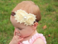 Cream flowers accented with a pearl and rhinestone center have a beautiful vintage feel on a brown lace elastic band. Perfect for many occasions, simple enough for every day but easy to dress up for a formal event like wedding or photos. $6.50 from www.etsy.com/shop/bellagraziadesigns