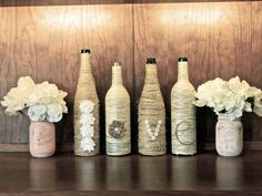 Four hand decorated wine bottles wrapped in jute twine (white and tan) spelling out the word LOVE with flowers, buttons, and trim. If you would
