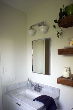 Tiny master bath remodel with vintage-inspired lighting, carrara marble top, and rustic shelving.