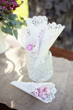 Cups of flower petals for the wedding guests to throw. The cups are made from pretty paper doilies and would be so easy to make!