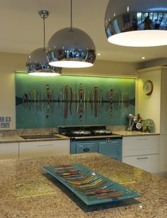 This particular bespoke splashback in Kent measures 2.4 m x 1.0 m with the joints of the piece being precision cut. This leaves a neat finish. This particular piece uses a Dalaman design with ocean hues all contributing to the piece including many blues and yellows. To accompany, orange is also added to the piece and fits well with the stove, creating a uniform look that transforms the kitchen and gives it a definite style!