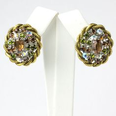These colorful 1950s earrings by Christian Dior feature golden topaz, green tourmaline and AB diamanté surrounded by textured gold-plated ropes.