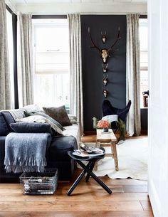 animal skull deer heads on dark gray wall, mid century mod chair, faux hide rug, gray sofa, hardwood floor, tri leg table, bench as coffee table