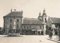 """Székesfehérvár, Fő tér. """"1935-ben. A Fő tér a püspökkúttal. (korabeli nevén: Károly király tér.) A képen kisiparos üzletsor (gyógyszertár, Héjj Testvérek, Montskó Flórián, Ulmann József, Szathmáry József) és egy benzinkút is látható az akkori Bierbauer ház előtt. A teret 1936-ban kezdték átépíteni. A mai Városház térről van szó. Hungary, Taj Mahal, Florida, Mansions, House Styles, Building, Travel, Decor, Viajes"""