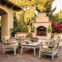 Weathered teak furnishings topped with durable cushions and fabrics make the entry courtyard a favorite spot for entertaining. #entertaining #patios #phgmag