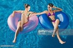 Stock-Foto : Two young women floating on inner tube in swimming pool, smiling, elevated view